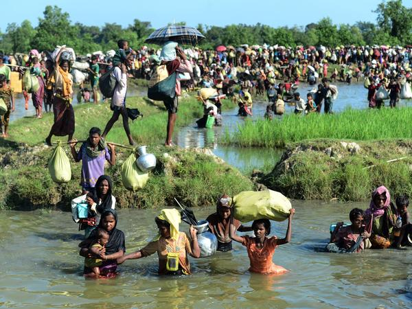 Rohingya refugees walk through a shallow canal after crossing the Naf River to reach Bangladesh on Monday. The U.N. has said that 537,000 Rohingya have arrived in Bangladesh over the past seven weeks. They are fleeing violence in Myanmar's Rakhine State, where the United Nations has accused troops of waging an ethnic cleansing campaign against them.