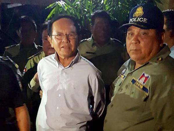 Cambodian opposition leader Kem Sokha (left) is taken by police from his home in Phnom Penh on Sept. 3. He was arrested and charged with treason. He denies the charges.