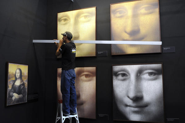 A worker hangs replicas of Leonardo da Vinci's Mona Lisa at a 2009 exhibition in Medellin, Colombia. (Luis Benavides/AP)