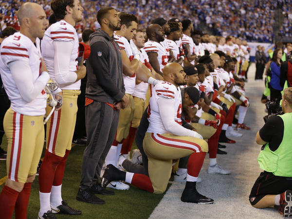 Members of the San Francisco 49ers kneel during the playing of the national anthem before an NFL football game against the Indianapolis Colts, earlier this month.