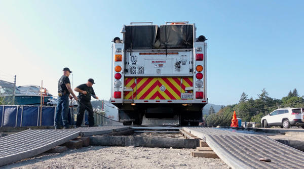 <p>Fire crews spray off a fire engine used on the Chetco Bar fire. They're trying to prevent the spread of the plant disease, Sudden Oak Death, to other states.</p>