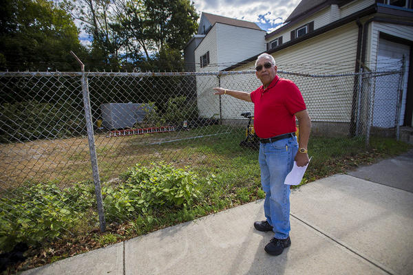Nick Schuyler points at the vacant lot where his home used to be. (Jesse Costa/WBUR)