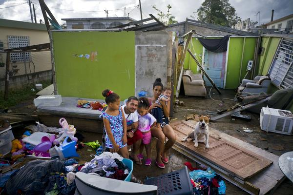 Arden Dragoni, second from left, poses with his wife Sindy, their three children and dog Max, surrounded by what remains of their home destroyed by Hurricane Maria in Toa Baja, Puerto Rico. They lost everything: clothes, household goods, and an old car.