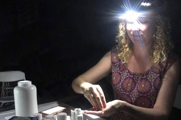 USF Health physician Asa Oxner works without power in Puerto Rico with only the illumination from a head lamp.