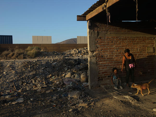 Aurelia Rodriguez and her daughter Melanie stand in a structure in Tijuana, Mexico, with a view of border wall prototypes under construction.