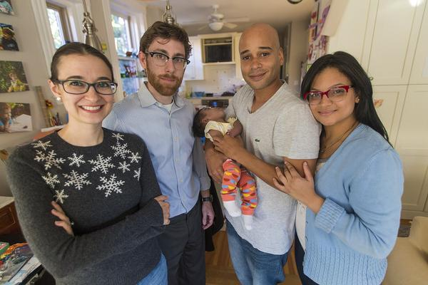From left: Host family members Gwen Taylor and Jeff Lindy stand with Kelvin Garcia, holding Amaia, and Alianette Andino. (Jesse Costa/WBUR)