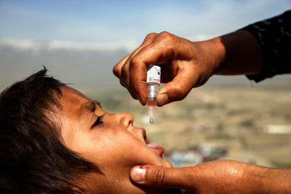 An Afghan health worker vaccinates a child as part of a campaign to eliminate polio, on the outskirts of Kabul, Afghanistan, in April 2017.