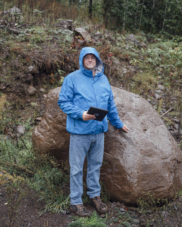 Bill Burns stands next to a large boulder that came down from the hillsides in a 1996 landslide in the Columbia River Gorge.
