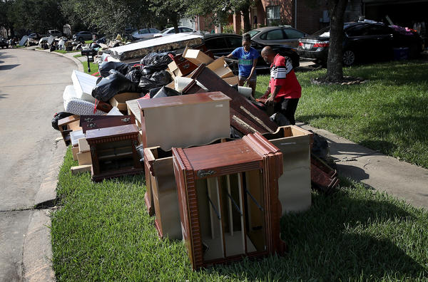 People discard possessions last month that were damaged by flooding brought on by Hurricane Harvey in Dickinson, Texas.