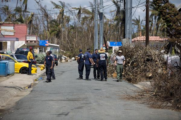 A group consisting of the Chicago Fire Department and Puerto Rico Fire Corps arrive on the scene to assist residents on Cll 19 in Punta Santiago. (Jesse Costa/WBUR)