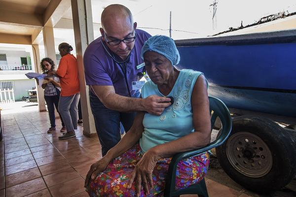 As part of the relief effort by El Programa de Educación Comunal de Entrega y Servicio (PECES), a HIMAHEALTH volunteer Dr. Martin Agüero examines 74-year-old Arsenia Montañez Pizzarro at her home in Punta Santiago. (Jesse Costa/WBUR)