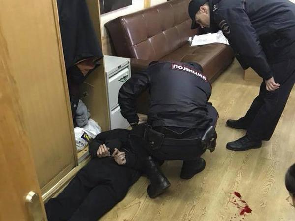 Police officers detain a man who reportedly stabbed journalist Tatyana Felgenhauer on Monday.