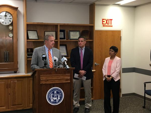 Onondaga County Health Commissioner Dr. Indu Gupta (right) and state health department Deputy Commissioner Brad Hutton (center) speak Monday about Mumps cases at Syracuse University. At the podium is Dolan Evanovich from Syracuse University.