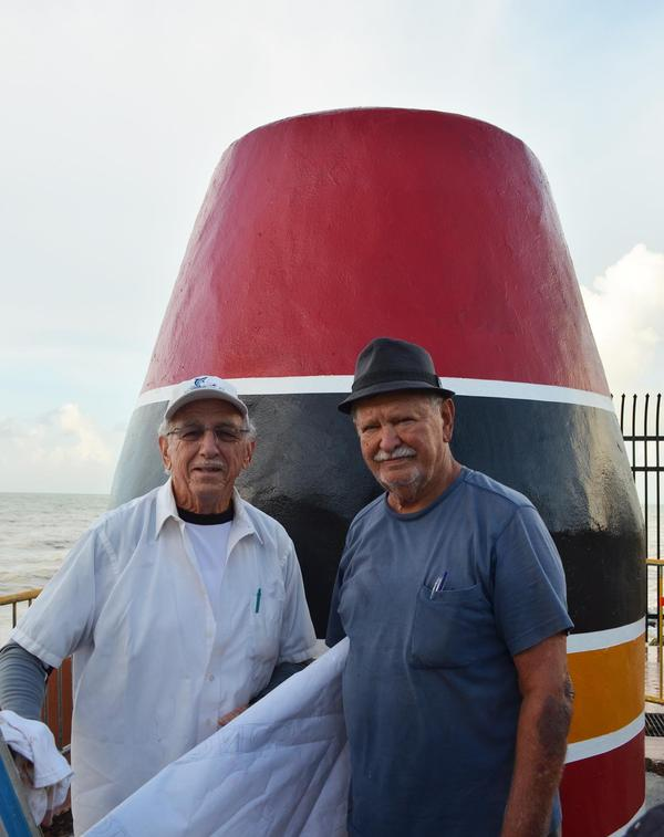 Danny Acosta (left), the artist who first painted the iconic buoy,  teamed up with Henry DelValle to restore the Southernmost Point marker.