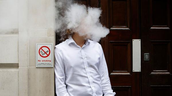 The state of New York is putting e-cigarettes into the same category as regular tobacco cigarettes, under new restrictions signed into law this week. Here, a man uses a vape device in London last summer, next to a No Smoking sign.