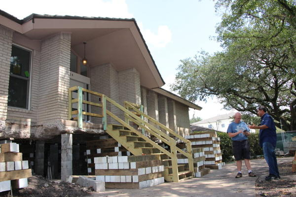 After privately funding his own elevation, Meyerland homeowner Drew Shefman (left) said his home was lifted to nearly 5 feet — one day before Harvey hit. (Allison Lee/Houston Public Media)