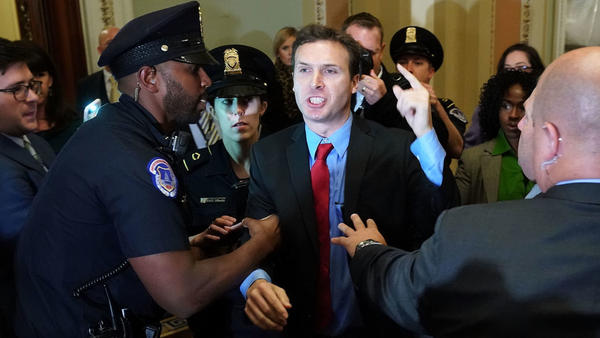 Ryan Clayton of Americans Take Action is corralled by police after he threw Russian flags at Senate Majority Leader Mitch McConnell and President Trump as they arrived for the Republican Senate Policy Luncheon at the Capitol.