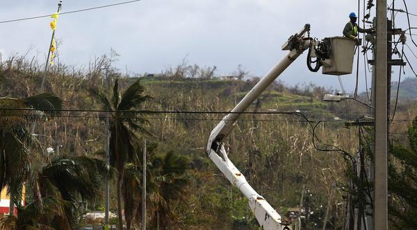 A worker repairs power lines about two weeks after Hurricane Maria swept through the island on Oct. 5, 2017 in San Isidro, Puerto Rico. (Mario Tama/Getty Images)