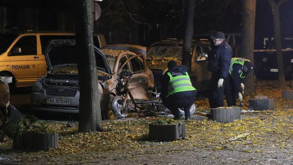 Police officers examine the crime scene where a Ukrainian lawmaker was wounded and his bodyguard killed in Kiev late Wednesday night.