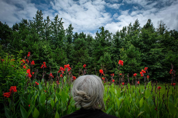 The photographer's aunt Jean stands in front canna lilies in Dalark, Arkansas.