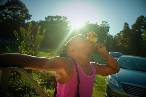 "The photographer's cousin Miyah eats a caramel apple days before Halloween. The picture is part of the series, ""Not Forgotten: An Arkansas Family Album."""
