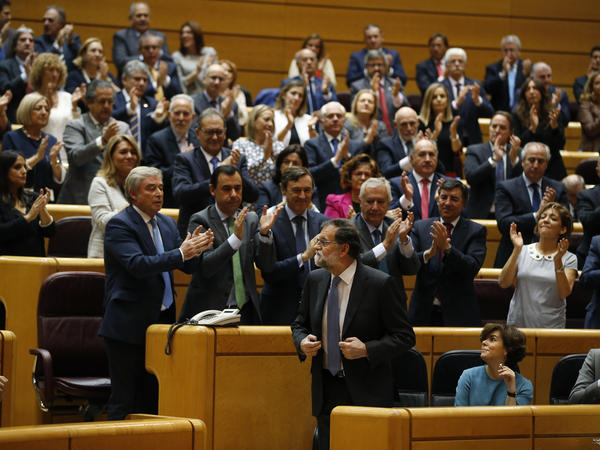 Spanish Prime Minister Mariano Rajoy (center) is applauded after a speech in Madrid on Friday in which he appealed to the country's Senate to grant special authority to dissolve Catalonia's regional government.