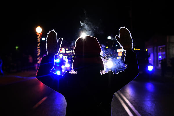 A protester holds her hands up in front of a police car in Ferguson, Mo., on November 25, 2014.