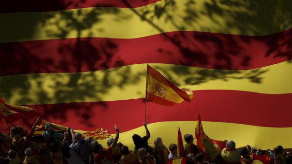 A nationalist activist waves a Spanish flag in front of a giant Catalan flag during a mass rally against Catalonia's declaration of independence, in Barcelona on Sunday.