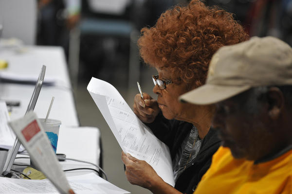 A homeowner uses a magnifying glass to read the fine print on a document as she meets with bank representatives in the hopes of renegotiating and lowering her mortgage payments at an event organized by the non-profit organization Neighborhood Assistance Corporation of America (NACA) at the Los Angeles Convention Center on September 28, 2009. NACA provides the opportunity for borrowers to meet with counselors and bank representatives on the spot to renegotiate their loan terms and prevent foreclosure on their home.