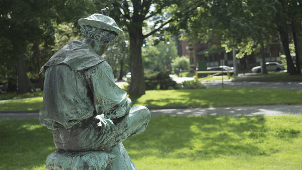 A figure of Sam Colt as a boy sits in front of the statue of Colt in his prime, in Hartford's Colt Park.