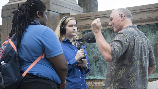 Student reporters Madyson Frame (left) and Nicole Ellis interview historian Bill Hosley at the Colt Memorial Statue in Hartford's Colt Park