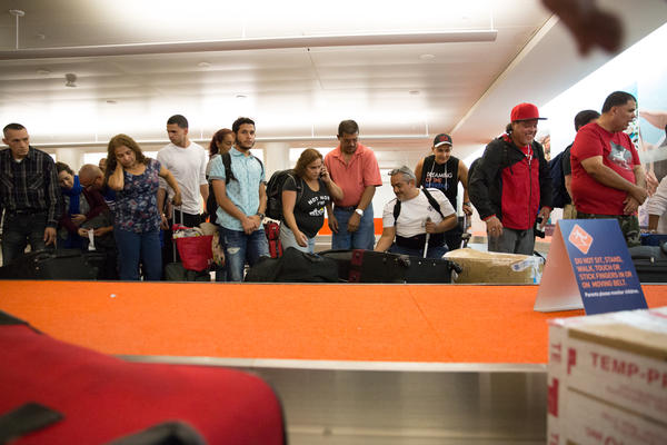 Passengers from a direct flight from Bradley International Airport wait to pick up their checked baggage -- much of it cardboard boxes full of supplies -- in the San Juan Airport.