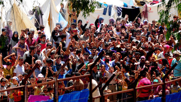 <p>Syrian refugees gather to protest Syrian President Bashar Assad at the Turkish Red Crescent camp in the Yayladagi district of the Turkish city of Hatay near the Syrian border on June 20. More than 7,000 Syrians are living in camps in Turkey.</p>