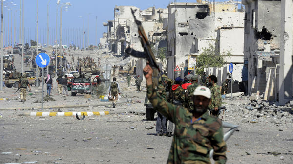 <p>In Sirte, fighters loyal to the new government celebrate after the town's defenses finally fell, and former leader Moammar Gadhafi was killed.</p>