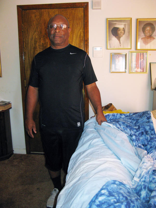 "<p> Robert Frazier of Suisun City, Calif., is seen at home with a prototype of ""The Pouch,"" a sleeping bag attached to a fitted sheet, so that both fit over a mattress. He has a patent, but he doesn't want to take production to China or India.</p>"