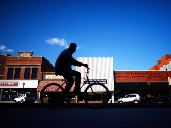 A biker rides through downtown Ponca City, Okla. After 726 complaints and close to $20 million in settled lawsuits against Continental Carbon, there are very few reports of black dust tainting the town.