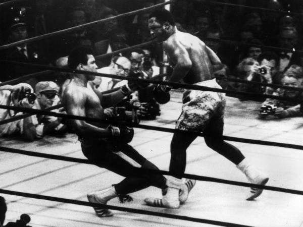 Muhammad Ali (right) goes down in the 15th round of a title fight in 1971 to a left hook from world heavyweight champion Joe Frazier.