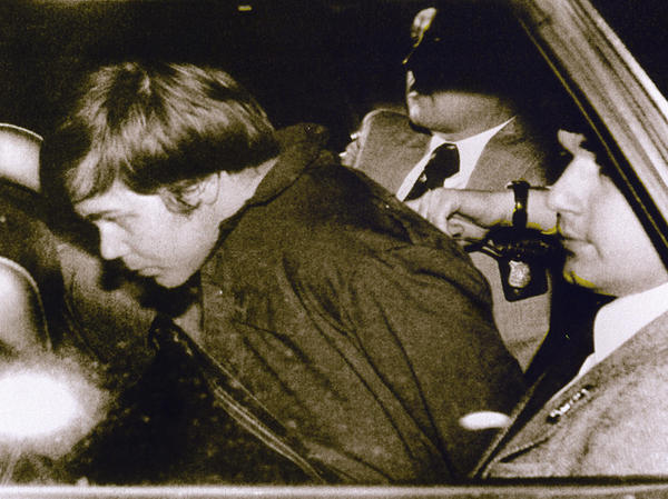 John Hinckley Jr. is escorted by police in Washington, D.C., on March 30, 1981, following his arrest after shooting and seriously wounding then-President Ronald Reagan.