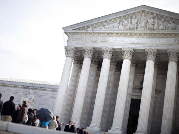 People wait to enter outside the U.S. Supreme Court in March. The court hears arguments Wednesday in a case testing whether the federal government is liable for damages when it violates the Privacy Act by disclosing that an individual is HIV-positive.