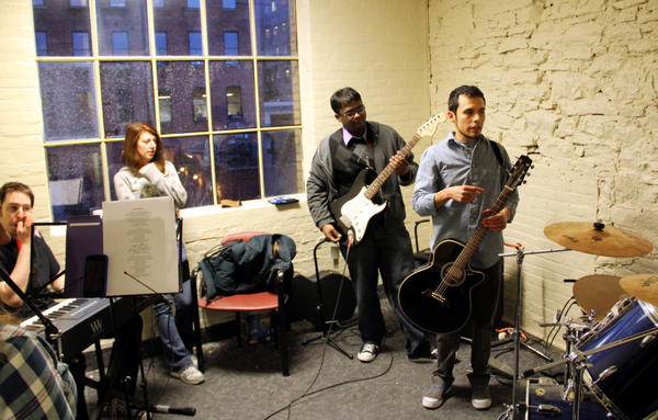 Music educator Ivan Trevino (right) leads band practice for M5 Networks employees in Rochester, N.Y., who will play against other branches in a battle of the bands. The telecom company says it wants its employees to learn new things (and stay happy).