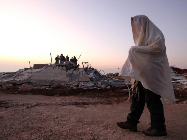 A Jewish settler wears his prayer shawl as he passes one of the structures demolished at the unauthorized Jewish settlement outpost in Ramat Migron, in the West Bank, on Sept. 5, 2011. Israel's radical Hilltop Youth have built numerous such outposts in recent years.