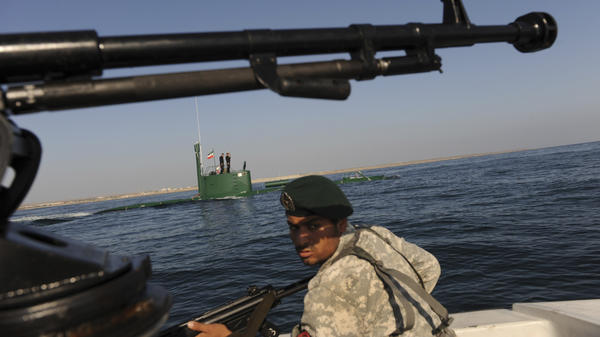 A member of Iran's navy participates in a drill on Dec. 28, 2011, in the Sea of Oman. Tehran is threatening to close the strategic Strait of Hormuz at the mouth of the Persian Gulf, in retaliation for new sanctions by the West.