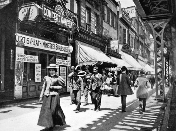 The Bowery, under the shadow of the elevated train tracks in New York City, bustled at night with colored lights and cane-swirling barkers, in places such as the Lyceum Concert Garden.