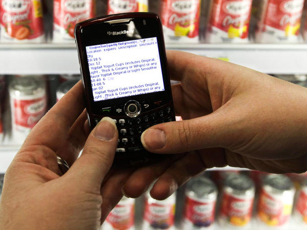 A shopper searches on her BlackBerry for coupons inside a Target store. Consumers with smartphones are changing the way stores set prices and track customer tastes.