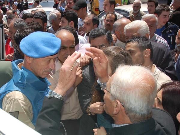 A U.N. observer (left) speaks with Syrian citizens during their visit to the pro-Syrian regime neighborhoods, in Homs province, central Syria, on April 23.