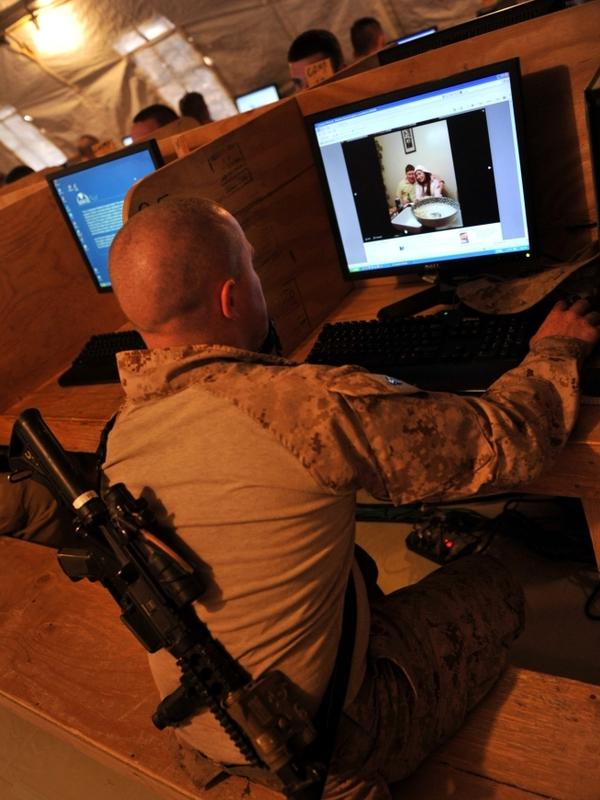At Forward Operating Base Payne in Afghanistan's Helmand province, Marine Cpl. Jonathan Odriscoll looks at pictures of his sister on Facebook. Troop access to social media has been both a blessing and curse for the military.