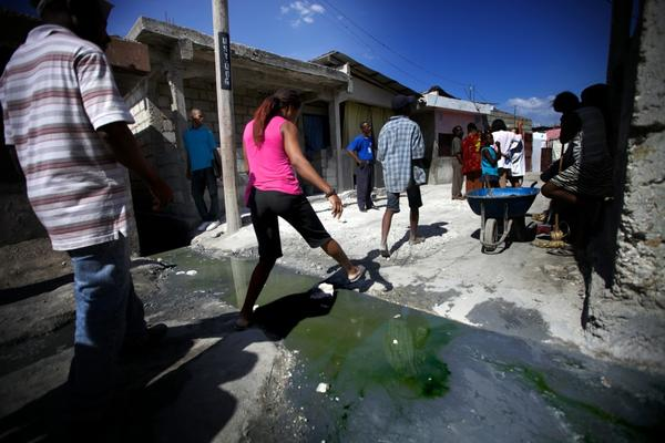 Residents of the Port-au-Prince slum Cite de Dieu step gingerly over a stream of sewage. Aid workers had planned to be finished with the vaccination program before the spring rains, when widespread flooding can bring cholera directly into people's homes.