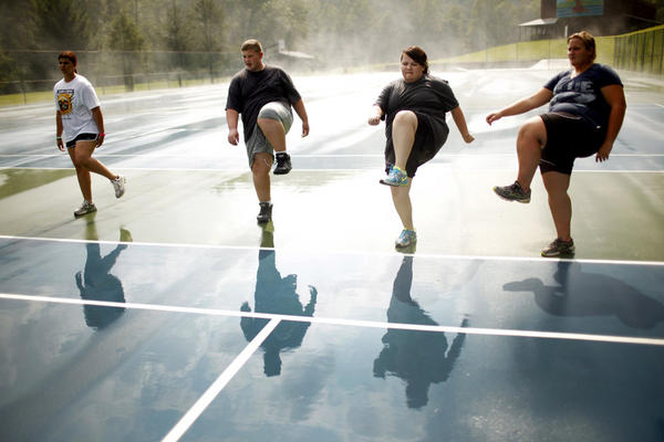 Students do high steps on the tennis court. Exercise is paramount at Wellspring, and a little rain doesn't get in the way of outdoor activities.