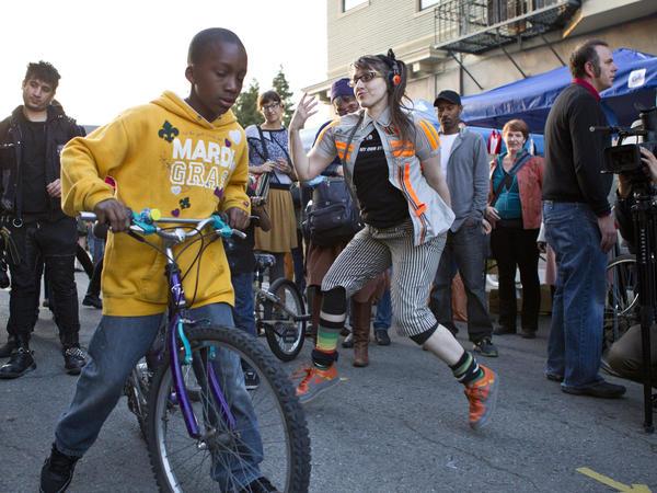 A performance artist dances on 23rd Street in Oakland as First Friday Art Walk attendees pass by.