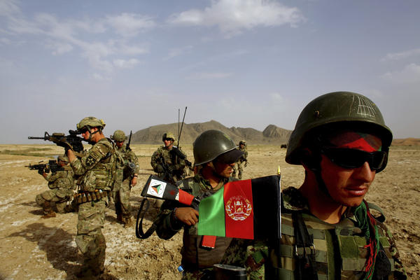 Afghan soldiers (right) patrol with U.S. troops in the Panjwai district of southern Afghanistan in May. The two armies have been working together for years, but Afghan attacks against U.S. and NATO forces have been rising recently.